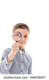 Closeup of a beautiful child looking through a magnifying glass loop over white background