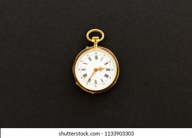 Closeup of a beautiful classic gold pocket watch on black background.