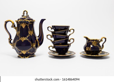 Closeup of a beautiful cobalt blue colored vintage porcelain tea set with golden floral pattern on white background. The set includes a tea pot, a milk jug and a stack of tea cups.