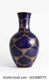 Closeup of a beautiful cobalt blue colored vintage porcelain vase with golden floral pattern on white background