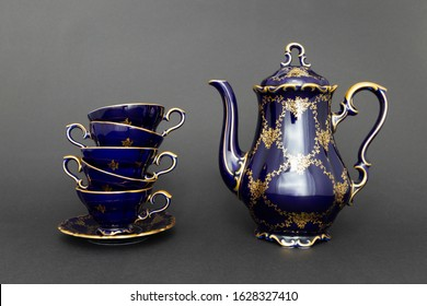 Closeup of a beautiful cobalt blue colored vintage porcelain tea set with golden floral pattern on dark gray background. The set includes a tea pot, and a stack of tea cups.