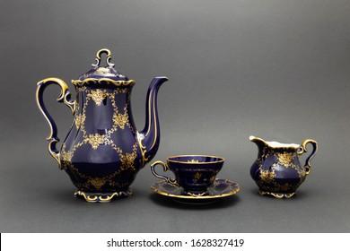 Closeup of a beautiful cobalt blue colored vintage porcelain tea set with golden floral pattern on dark gray background. The set includes a tea pot, a milk jug and a tea cup.