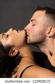 Closeup of a beautiful couple. A man sensually touches his lips to the chin of a girl whose shoulder is bare. Casual fashionable style. Lifestyle, fashion, commercial design. Gray background.