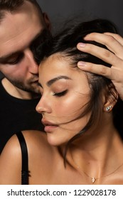 Closeup of a beautiful couple. A man sensually touches his lips to the forehead of a girl whose shoulder is bare. Casual fashionable style. Lifestyle, fashion, commercial design. Gray background.