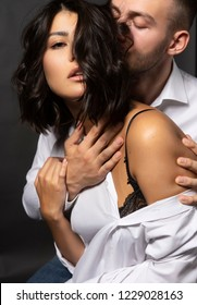 Closeup of a beautiful couple wearing white shirts. A man passionately touches his lips to the girl's hair. Casual fashionable style. Lifestyle, love, commercial design. Gray background.