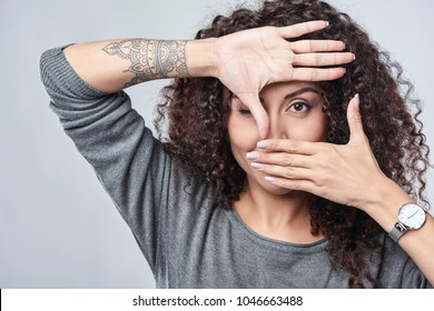 Closeup of beautiful curly woman making frame with hands over grey background