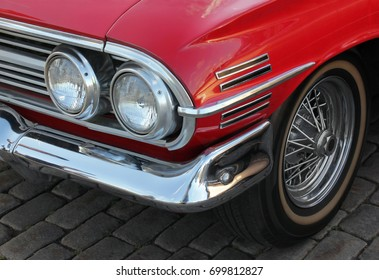 A closeup of beautiful details of vintage red car on the front side.