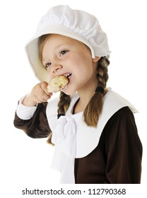Closeup of a beautiful elementary Pilgrim girl happily enjoying a small drumstick.  On a white background.