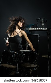 Closeup of beautiful emotional expressive cool young brunette sexual rock musician woman with long curly hair standing in recording studio playing drums with sticks near electro guitar and microphone