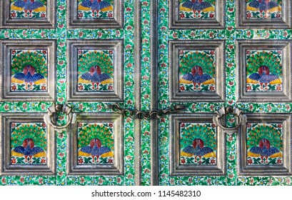 Close-up of beautiful enameled door with flowers and peacocks in frames locked up tight with a chain