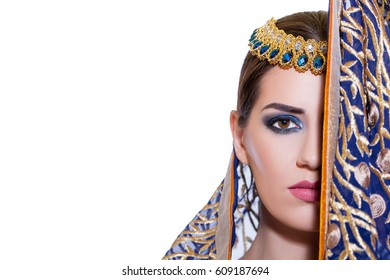 Closeup Beautiful Fashion Arabian girl in hijab. Beauty Portrait Arab or Indian woman Wears expensive blue clothes embroidered with gold. Isolated on white background.   Woman in National Clothes