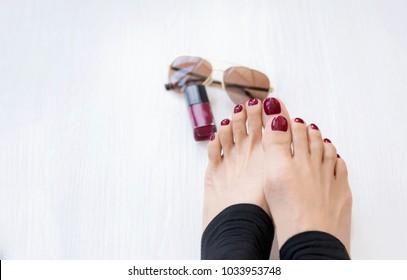 da188e888ed8 Closeup of Beautiful female feet with blurry nail varnish in dark cherry  colour and sun glasses