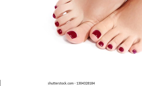 Close-up Beautiful Female Feet with Red Pedicure. Clean Soft Skin, Healthy Nails with Gel Polish. Copy Space on White Background