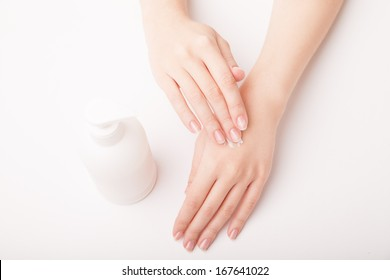 Closeup of beautiful female hand applying hand cream