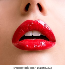Closeup beautiful female lips with red lipstick. Glamour fashion bright gloss make-up.