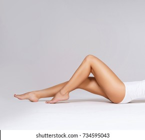 Close-up of beautiful, fit and sporty legs isolated on white. Health, sport, fitness, epilation, cellulite and hair removal, liposuction, healthy life-style concept.