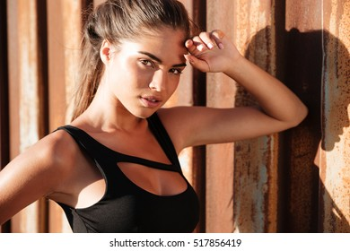 Closeup of beautiful girl in black top with natural makeup over rusty metal background