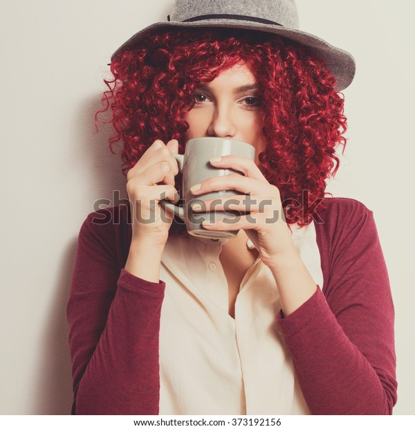 Closeup of beautiful girl with red curly hair in gray floppy hat, beige shirt and red cardigan drinking coffee or tea from gray mug. Modern young woman drinking hot beverage. Square format, filter.