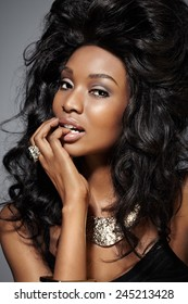 Closeup of a beautiful glamorous dark woman wearing large ring and choker.
