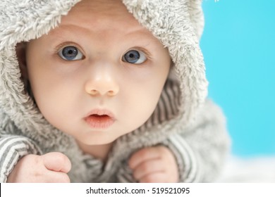 closeup of beautiful happy baby with blue eyes in grey bear like clothing on blue background