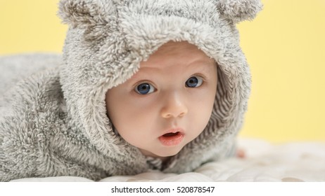 closeup of beautiful happy baby with blue eyes in grey bear like clothing on yellow background