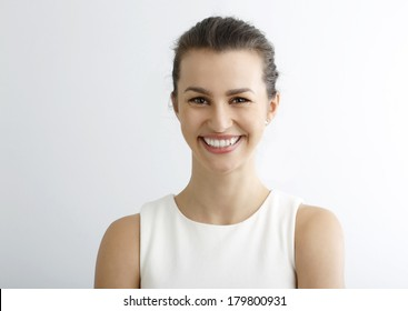 Close-up of beautiful happy woman looking at camera against white background.