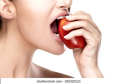 Closeup of beautiful and healthy mouth biting a red apple. Closeup portrait isolated on white background. Clean eating