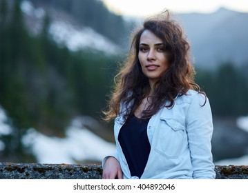 Closeup of a beautiful hispanic woman outdoor near a pine forest and mountains