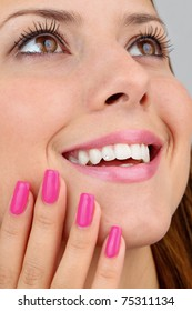 Closeup of  a beautiful lady with healthy smile, dental jewelry, long eyelashes and manicured nails. Intentional shallow depth of field.