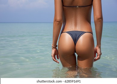 Close-up beautiful luxury slim back of a beautiful woman in a swimsuit posing in the sea water. Sexy tanned body, flat stomach, perfect figure. Rest on a tropical island. Sexy buttocks. With copyspace