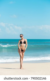 Close-up beautiful luxury slim girl in a black bikini on the beach the ocean. Outdoor summer lifestyle image of young pretty woman outfit and sunglasses, fun ,joy, emotions.