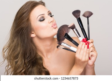 Closeup of beautiful makeup lover and makeup artist woman holding various brushes. Studio lighting, no retouched, closeup.