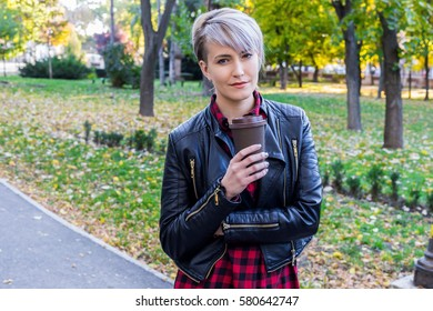 Closeup of beautiful millennial teenage girl in park in spring with takeaway coffee, smiling, looking at camera. Natural light, mild retouch.