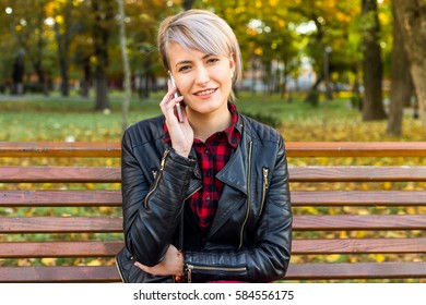 Closeup of beautiful millennial teenage girl in park in spring, talking at her smart phone, smiling, looking at camera. Natural light, mild retouch.