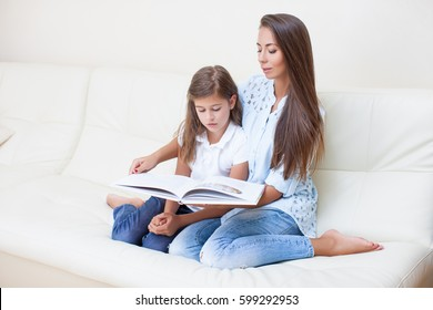 Closeup Beautiful Mom Teaches her Daughter on Vacation at Home, Home Study, Reading Books and Tests. Education and Child Development at Home