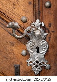Closeup of a beautiful old doorhandle and decoration made of silver on a brown door