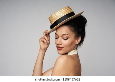 Closeup of beautiful playful mixed race caucasian - african american woman wearing chocker and canotier straw hat, isolated on gray background