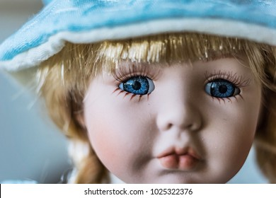 Close-up of beautiful porcelain doll with blond hair and blue eyes, sky blue vintage dress and leather shoes. Little princess games.