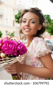 Closeup of beautiful pretty woman with bouquet of flowers. Outdoors