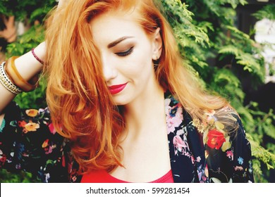 Closeup of beautiful red haired woman with matt red lips and eye makeup, eyeliner. Photo toned style instagram filters