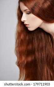 Closeup of beautiful red headed woman, over gray background