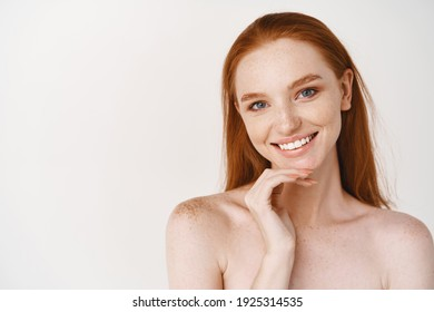 Close-up of beautiful redhead woman with pale skin, standing nude on white background, smiling with perfect teeth, touching clean no makeup face.