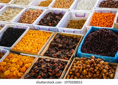 Close-up of beautiful rows of fresh nuts:  figs, raisins, dried apricots. Various nuts on the market showcase