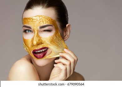 Closeup Beautiful Sexy Girl Taking Off Cosmetic Peeling Gold Mask From Healthy Skin.