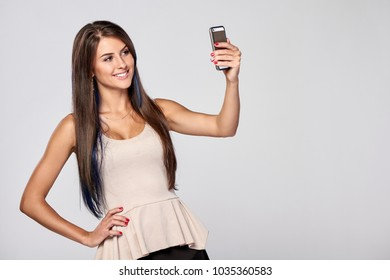 Closeup of beautiful smiling brunette woman taking self portrait on smart phone, over grey background