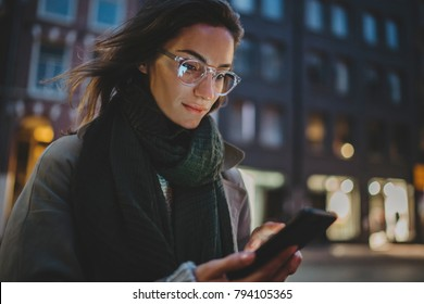 Closeup of beautiful smiling woman in glasses using modern smartphone device while walking in the night city streets, young happy traveler girl browsing the internet searching for landmarks