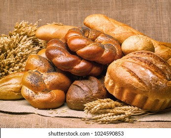 Closeup of a beautiful still-life from bread, pastry products with wheat ears, poppy seeds and buns on a background of burlap.