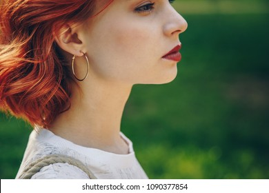 Close-up of a beautiful stylish woman wearing round gold earrings on a summer day outside