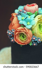 Close-up of beautiful and tasty homemade cake with sugar paste edible colorful floral decorations.