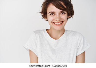 Nahaufnahme einer schönen und zarten Frau mit kurzen Haaren, lächeln und süß auf die Kamera schauen, mit T-Shirt, stehend auf weißem Hintergrund.